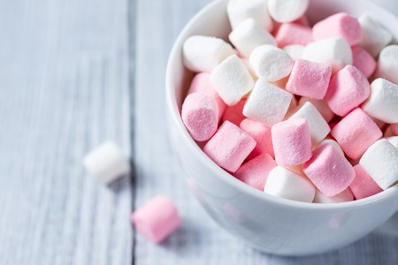 soft colors: Pink and white marshmallows in a cup, over wood background.