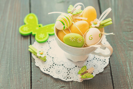 Easter egg in a tea cup, green and yellow colored photo