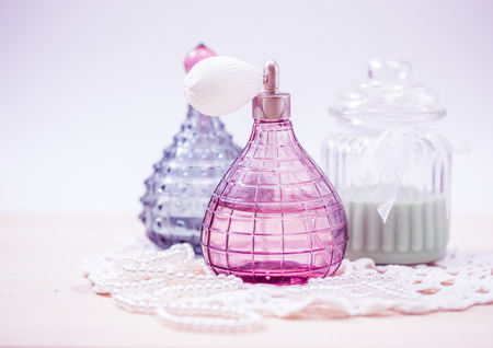 perfume spray: Two glass bottles of female perfume on a white background. Pink toning. Stock Photo