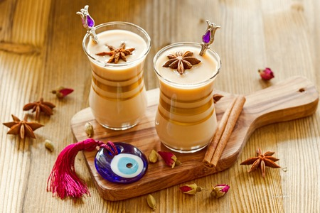 Masala tea in glass jars with spices and glass amulet Evil Eye
