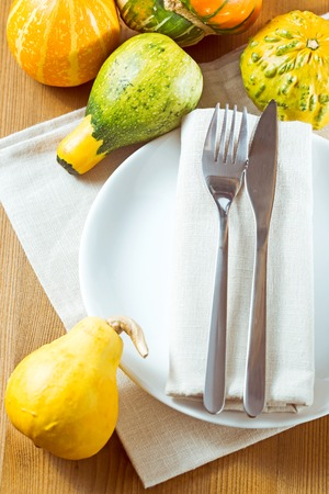 white linen: Autumn place setting with Pumpkins. Knife and fork with white linen tied up Stock Photo