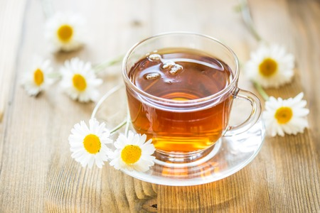 Cup of tea with chamomile flowers on rustic wooden background