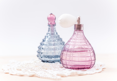 perfume woman: Two glass bottles of female perfume on a white background. Pink toning. Stock Photo