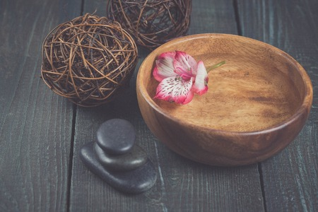 alstromeria: Beautiful spa setting with flower, spa stones on wooden background Stock Photo