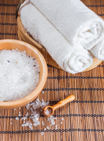 health care concept: Bath salt in a wooden bowl, three white towels and spa stones on a wooden background
