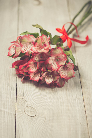 alstromeria: Spring decoration with pink alstromeria flowers of a wooden table. Vintage soft colours