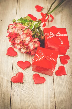 alstromeria: Red gift boxes, red hearts and bouquet of pink alstromeria flowers on white wooden background. Vintage soft colours