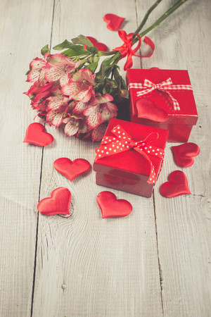 alstromeria: Red gift boxes, red hearts and bouquet of pink alstromeria flowers on white wooden background.