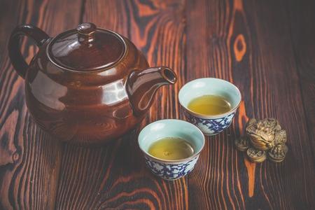 feier: Broun Keramik Teekanne und zwei Tassen für die Teezeremonie auf rustikalen Holztisch Lizenzfreie Bilder