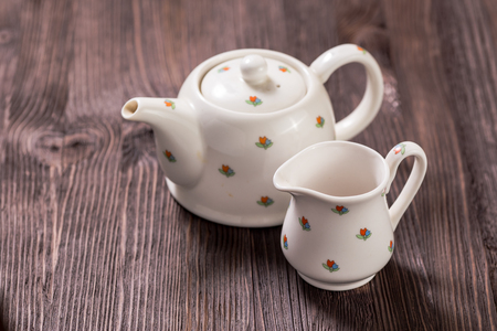 creamer: White ceramic teapot, creamer and sugar bowl on dark wooden background Stock Photo