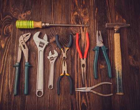 chisels: Different Working tools on a wooden table - a hammer, wire cutters, pliers, chisels and wrenches