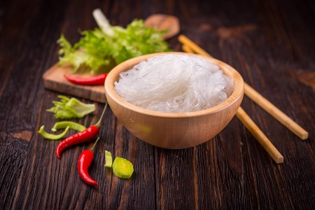 Ingredients of Asian cuisine - rice noodles, leek, lettuce, red hot pepper on a dark wooden background Standard-Bild
