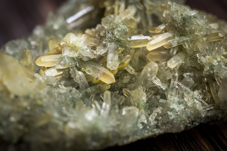 Druse green crystals of quartz on a dark wooden background Standard-Bild