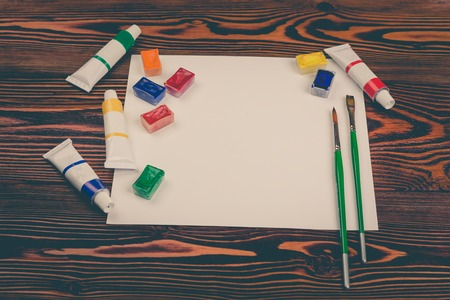 Sheet of paper, colored pencils, watercolor paints in tubes and cuvettes, brushes on a dark wooden table Foto de archivo