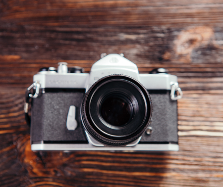 slide glass: Old film camera, lenses and old exposure meter on a wooden background