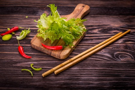 rice noodles: Ingredients of Asian cuisine - rice noodles, leek, lettuce, red hot pepper on a dark wooden background Stock Photo