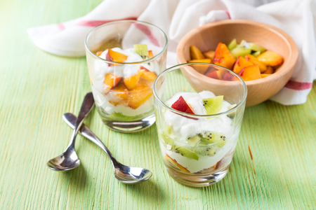 Fruit salad in glass goblets of kiwi and peaches with yogurt on green table Standard-Bild