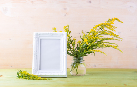 yellow wildflowers: Craft mockup set with Yellow wildflowers and white photo frame on a light wooden table Stock Photo