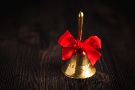 hand bell: Antique brass hand bell with a red bow on a dark wooden background