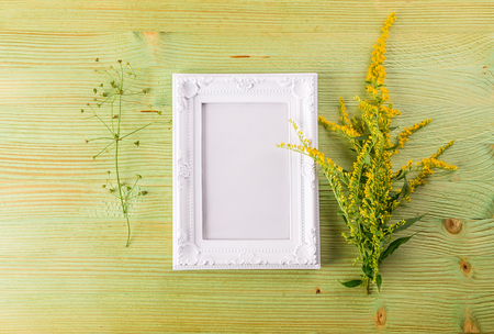 whitw: Craft mockup set with Yellow wild flowers and whitw photo frame on a light wooden table