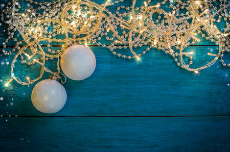 glowing christmas lights silver beads and a white christmas balls on a blue wooden background