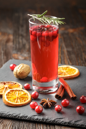 Christmas cranberry cocktail decorated with cinnamon sticks, anise stars, dry orange slices and rosemary