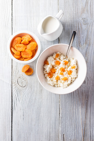 summer fruits: Breakfast from cottage cheese with slices of dried apricots in a white bowl on white wooden background. Free space for text . Top view