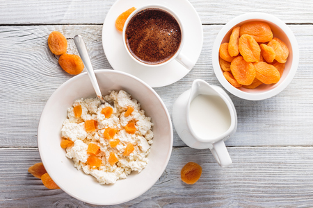 summer fruits: Breakfast from cottage cheese with slices of dried apricot and cup of black coffee on white wooden background. Top view Stock Photo