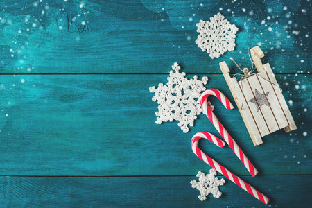 crocheted: Christmas candy canes, toy sledge, crocheted snowflakes and twigs spruce on a wooden background Stock Photo