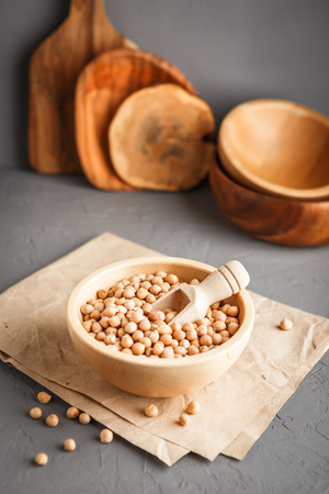 Wooden bowl with dry raw organic chickpeas on gray concrete background Stock Photo