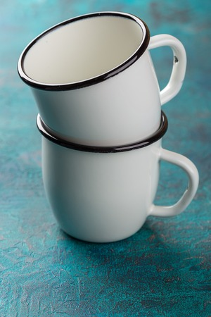 Two white enameled cup on a turquoise background