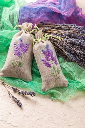 sachets: Two aromatic embroidered sachets filled with dried lavender and a bouquet of dry lavender