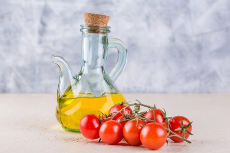 Ingredients for Italian cuisine - a bottle of vegetable oil and cherry tomatoes on a light background