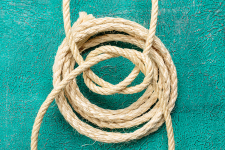 fixed line: Ship rope knot on turquoise background. Top view.