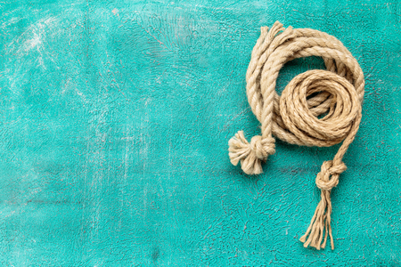 Ship rope knot on turquoise background. Top view. Place for text.