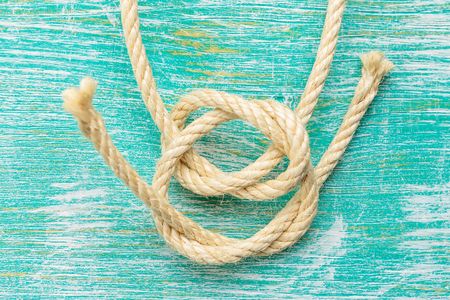 fixed line: Ship rope knot on turquoise wooden background. Top view.