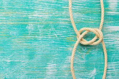 fixed line: Ship rope knot on turquoise wooden background. Top view. Place for text.