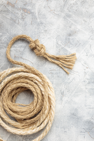 Ship rope knot on light gray concrete background. Top view. Place for text. Imagens - 76344056