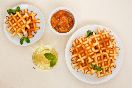 Belgian waffles on plate garnished with mint leaves, glass Cup of green tea with mint and peach jam with rosemary in small bowl on beige background. Top view