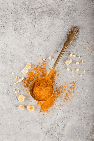 Different kinds of spices - cinnamon, caramelized brown sugar on gray concrete background. Top view.
