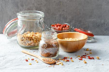 dietary fiber: Flax seeds, goji berries, granola, pine nuts in glass jars on gray background