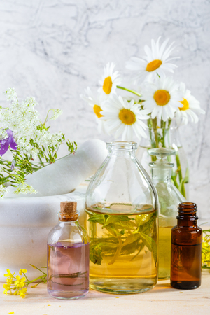 Mortar with fresh wild flowers and essential oil in glass bottles