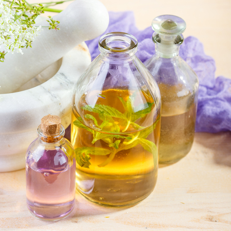 Bottles with natural aroma of essential oils, mortar and wild flowers, Spa concept. Stock Photo