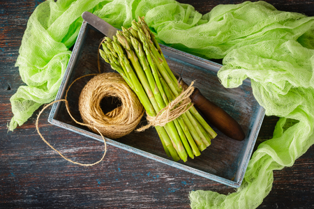 Raw asparagus, tangle of rope and knife in wooden box on dark wooden background Standard-Bild