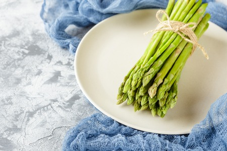 Bundle of raw asparagus on plate on light background