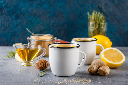 Two enameled cups with ginger-lemon tea, thyme, cinnamon, anise and honey on a gray background