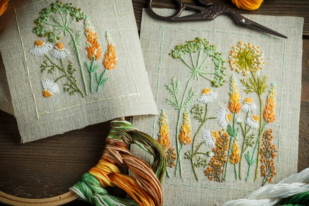 Schöne gestickte Arbeit, Thread, Schere, Holzrahmen auf einem hölzernen Hintergrund