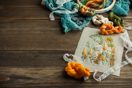 Beautiful embroidered work, thread, scissors, wooden hoop on a wooden background