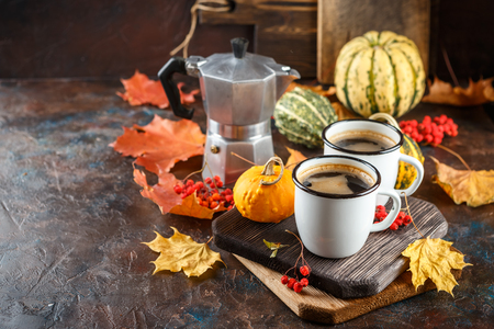 Autumn still life with enamel cups with coffee, pumpkins and maple leaves