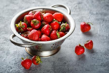 Fresh juicy appetizing strawberries in metal colander